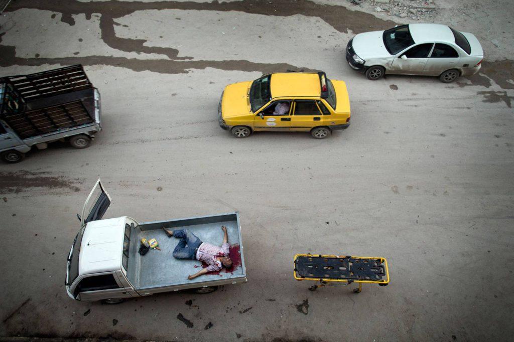 En död man har lastats på ett lastbilsflak i Aleppo. Foto: NICLAS HAMMARSTRÖM