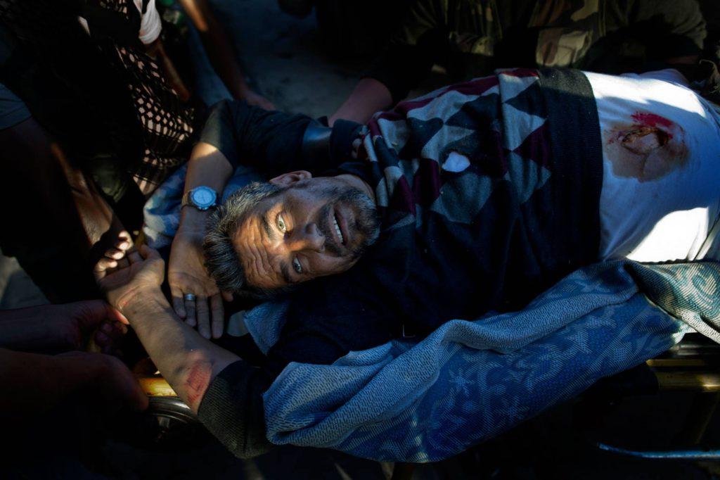 En krypskytt har skjutit mannen i ryggen. Han förs till Dar al-Shifa-sjukhuset av sina vänner. Foto: NICLAS HAMMARSTRÖM