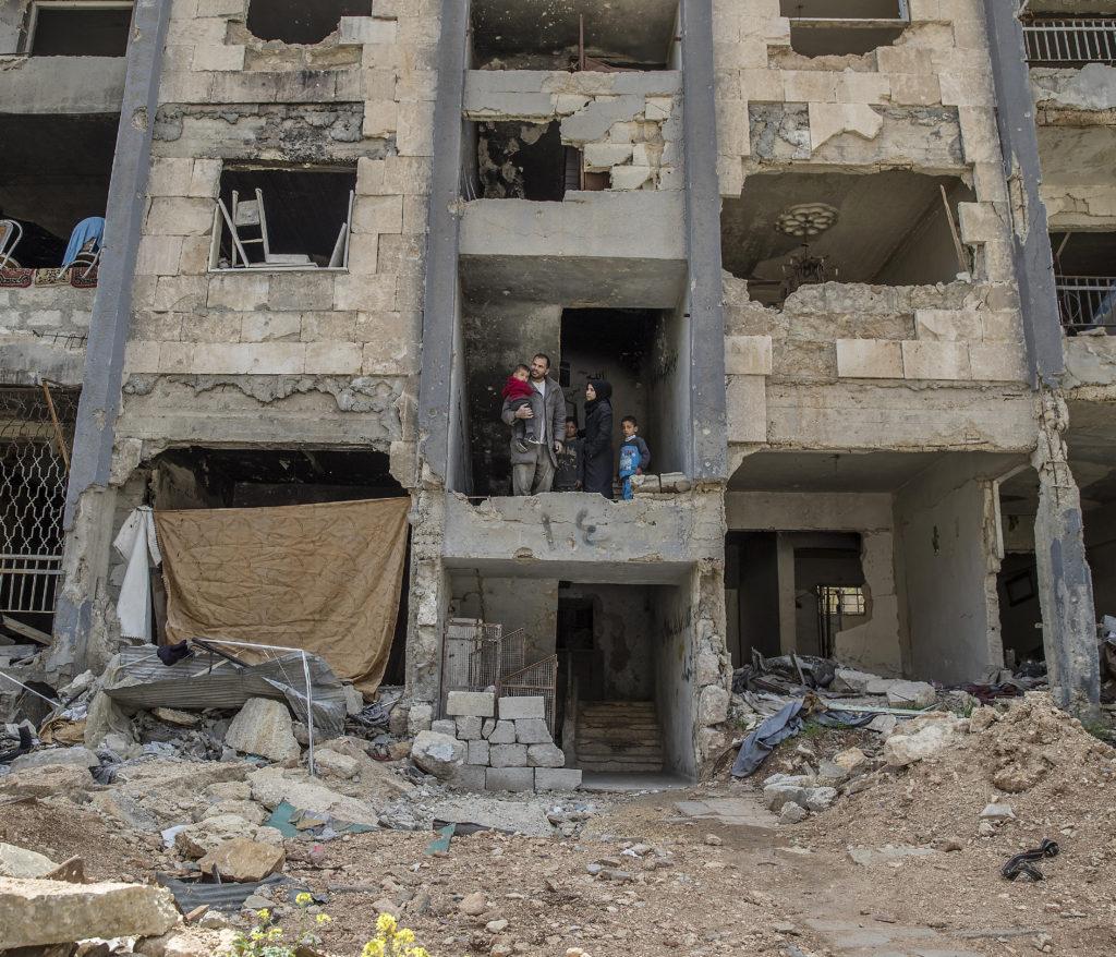 Familjen Qaddor är de enda som bor i höghuset i Hanano. Deras lägenhet är svart av sot, och väggen ut mot gatan saknas. Foto: MAGNUS WENNMAN